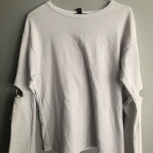 white sweater with silver circles on elbow cutout